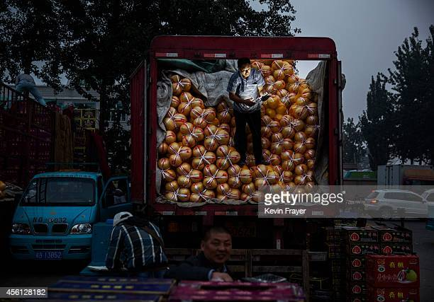 Chinese fruit vendor fixes a light as he stands on a truck at a local market on September 26 2014 in Beijing China China is challenged to ensure its...