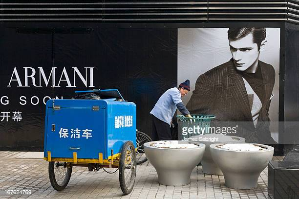 Chinese garbage man in blue workers' overalls empties the trash in front of the new Armani Store Beijing watched by the oversized image of a white...