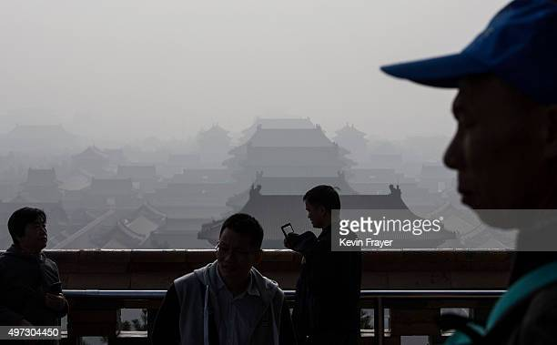 Chinese gathers as haze from smog caused by air pollution hangs over the Forbidden City on November 15 2015 in Beijing China As a result of industry...