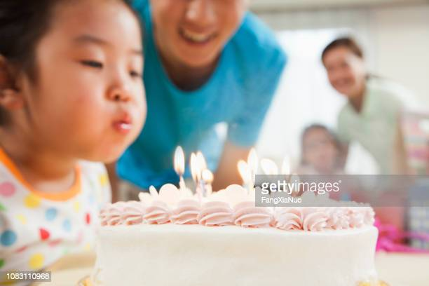chinese girl blowing out candles on birthday cake - happy birthday images for sister stock pictures, royalty-free photos & images