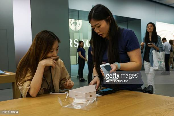 A Chinese girl buys an iPhone 8 Plus from an Apple showroom in Shanghai on September 22 2017 Apple iPhone 8 and 8 Plus went for sale in China...