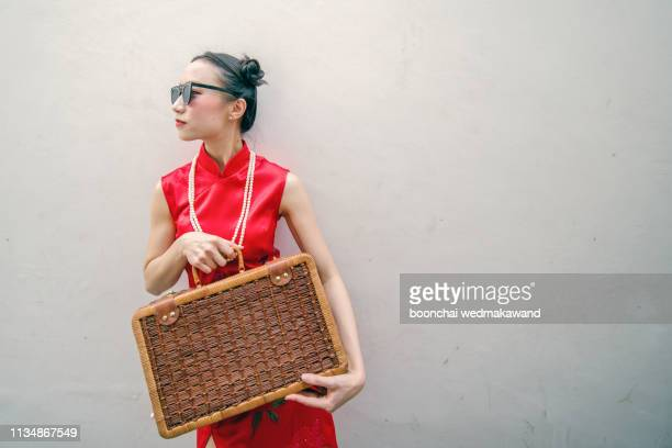 chinese girl carrying clothes bag - traditional clothing stock pictures, royalty-free photos & images