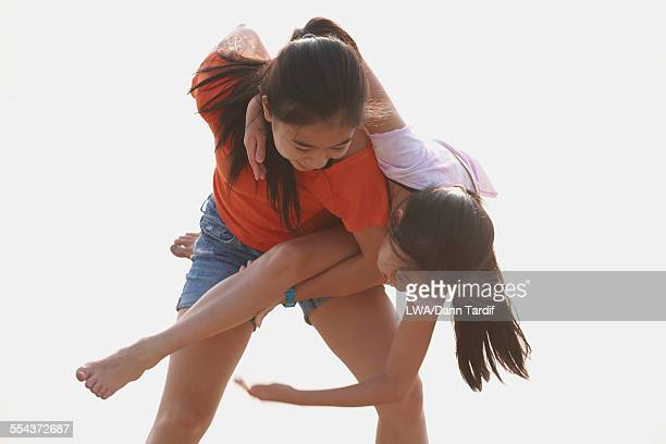 Chinese girl carrying sister piggyback on beach