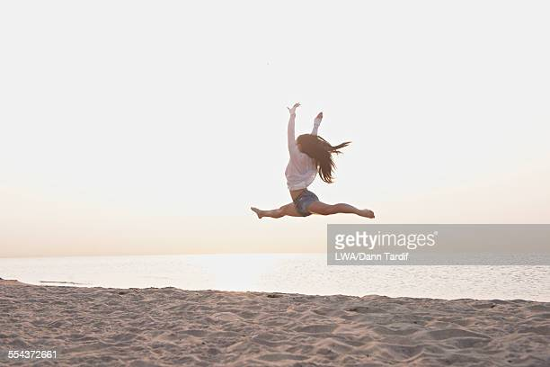 Chinese girl doing splits in mid-air on beach