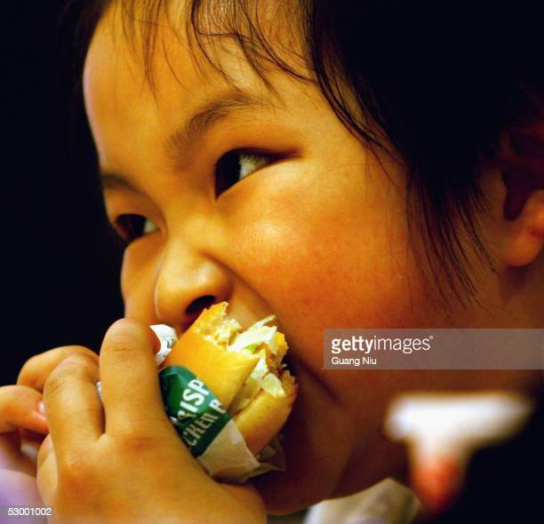 Chinese girl eats a hamburger at an American fast food chain for an activity to mark International Children's Day with her parents on May 31, 2005 in...