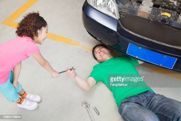 chinese girl handing father wrench - oil change stock pictures, royalty-free photos & images