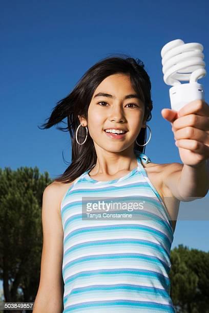 Chinese girl holding light bulb outdoors