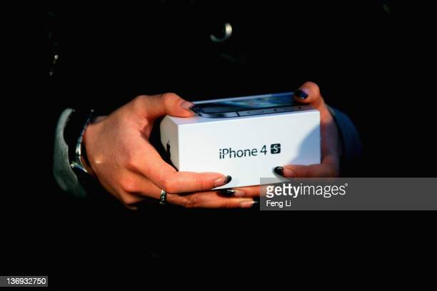 Chinese girl holds new iPhone 4S outside the Apple's Beijing flagship store on January 13 2012 in Beijing China Apple with China's leading...