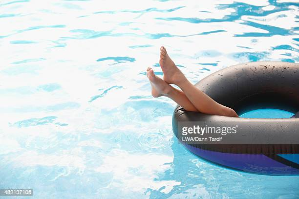 Chinese girl laying in inflatable ring in swimming pool