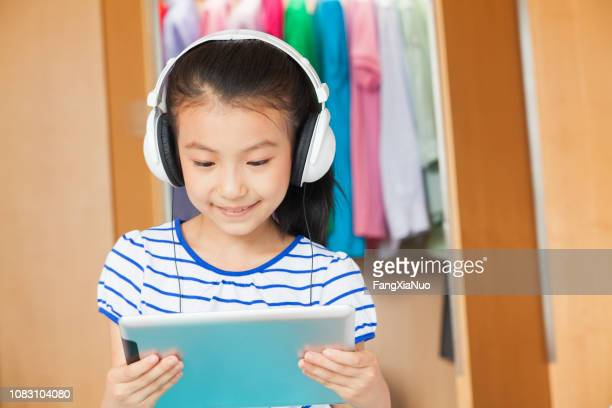 chinese girl listening to headphones with digital tablet - english language stock pictures, royalty-free photos & images