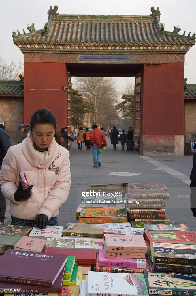 A Chinese girl looking for books at Ditan Park book fair, Beijing, China, Asia : Stock Photo