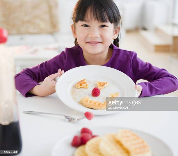 Chinese girl making a face on plate with waffle