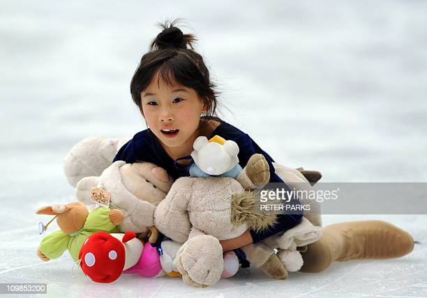 A Chinese girl picks up soft toys which were thrown by fans in the pairs final during the ISU Grand Prix of Figure Skating 2010 in Beijing on...