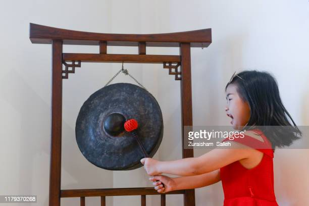 chinese girl plays the gong during chinese new year - gong stock pictures, royalty-free photos & images