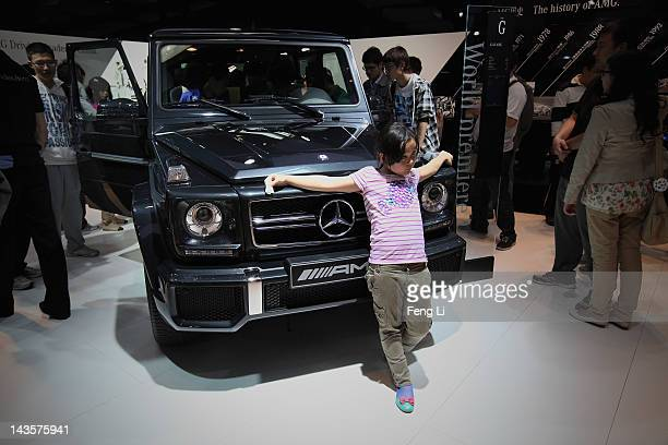 Chinese girl poses beside a MercedesBenz Class G 63 AMG car during the 2012 Beijing International Automotive Exhibition at China International...