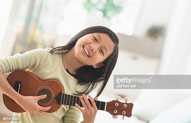 chinese girl practicing ukulele in bedroom - ukulele stock pictures, royalty-free photos & images