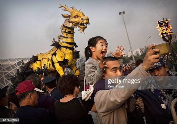 Chinese girl reacts as her father takes a picture of them in front of a large mechanical dragon called 'Dragon Horse' that is part of the Long Ma...
