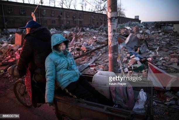 Chinese girl rides in the back of a scooter as it passes the rubble of buildings demolished by authorities in an area that used to have migrant...