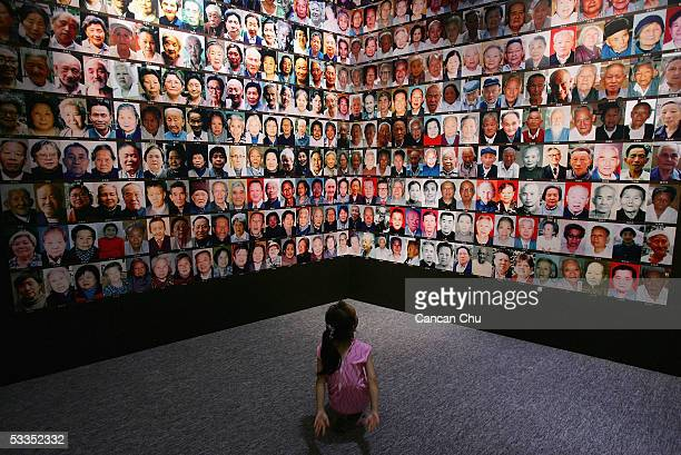Chinese girl views pictures of Nanjing Massacre survivors during an exhibition on the massacre at the National Museum August 11 2005 in Beijing China...