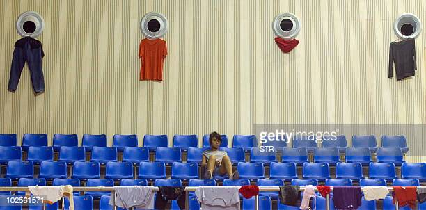 A Chinese girl waits for her laundry to dry at a flood relieve center in Fuzhou east China's Jiangxi province on June 24 2010 Heavy rains lashed...