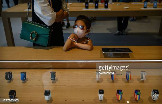 Chinese girl waits for her parent as they shop at the official opening of the new Apple Store in the Sanlitun shopping area on July 17 2020 in...