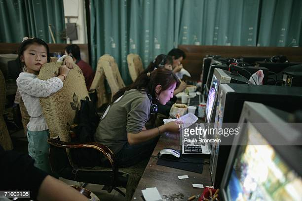 Chinese girl waits while her sister checks her email at a internet cafe on August 6 2006 in Lhasa of Tibet Autonomous Region China Lhasa's face is...