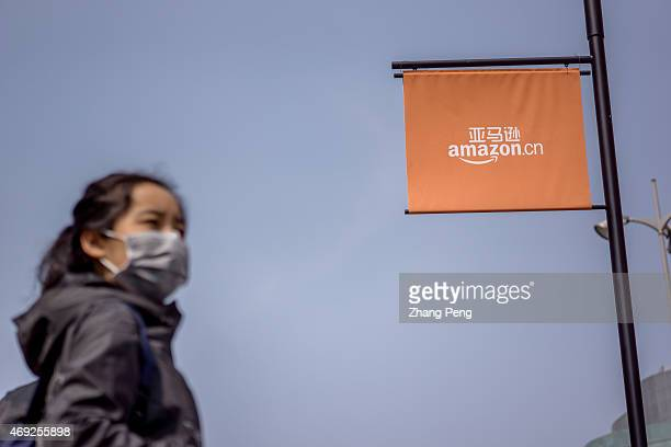 Chinese girl walks under the logo of Amazoncn The ebook readers in China increase greatly and Amazon's low cost strategy in Kindle seems very...