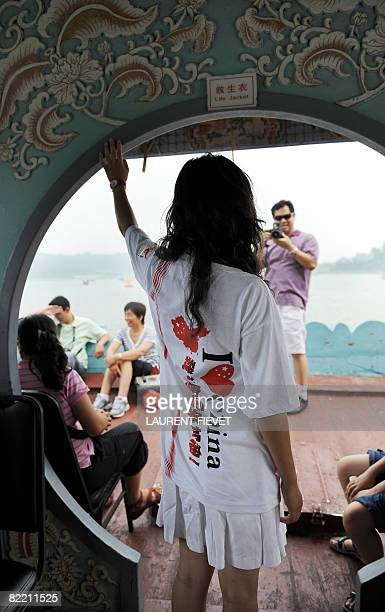 A Chinese girl wearing a I love China Tshirt poses for a photo while sailing on the Summer Palace lake hours before the opening ceremony of the 2008...