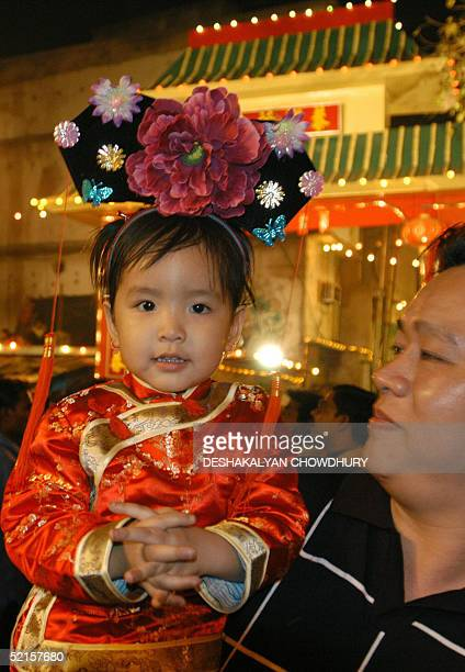 Chinese girl wearing new year cap watches the celebration of the Lunar New Year in China Town in Calcutta late 08 February 2005 The colourful dragon...
