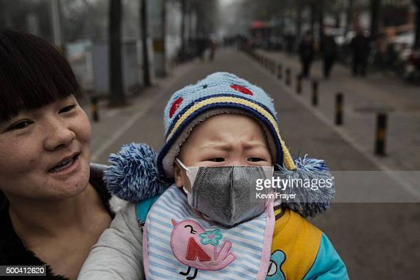 Chinese girl wears a mask as she is held by her mother outside a local hospital during a day of heavy smog on December 8, 2015 in Beijing, China. The...