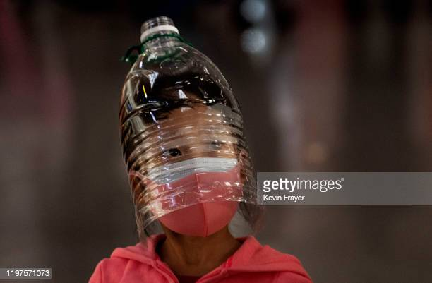 Chinese girl wears a plastic bottle as makeshift homemade protection and a protective mask while waiting to check in to a flight at Beijing Capital...