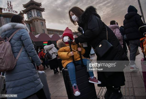 Chinese girl wears a protective mask as her mother pushes her on a suitcase to board a train at Beijing Railway station before the annual Spring...