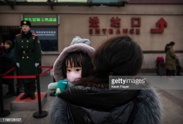 Chinese girl wears a protective mask as she is held by a relative as they wait to board a train at Beijing Railway station before the annual Spring...