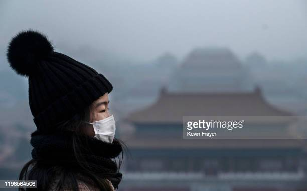 Chinese girl wears a protective mask as she stands on an overlook towards the Forbidden City which was closed by authorities during the Chinese New...