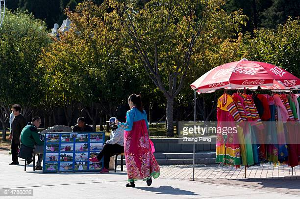 Chinese girl wears North Korea traditional clothes ready to take tourist photos. Dandong is the largest Chinese frontier city, bordering with Sinuiju...