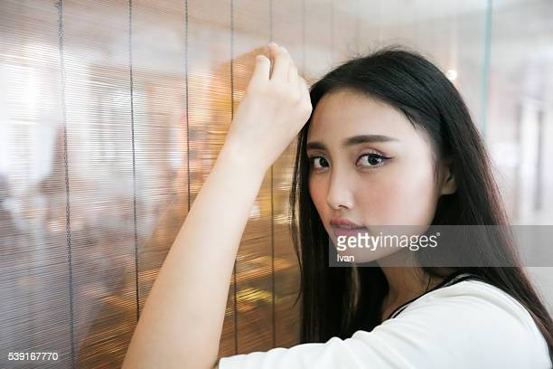 A Chinese Girl with Almond Eyes Looking Right Against Glass Window