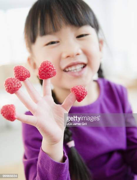 Chinese girl with raspberries on fingers
