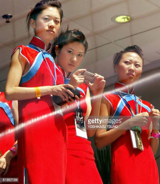 Chinese girls take pictures of Formula One drivers from the VIP room during a practice session for the F-1 China Grand Prix at the Shanghai...