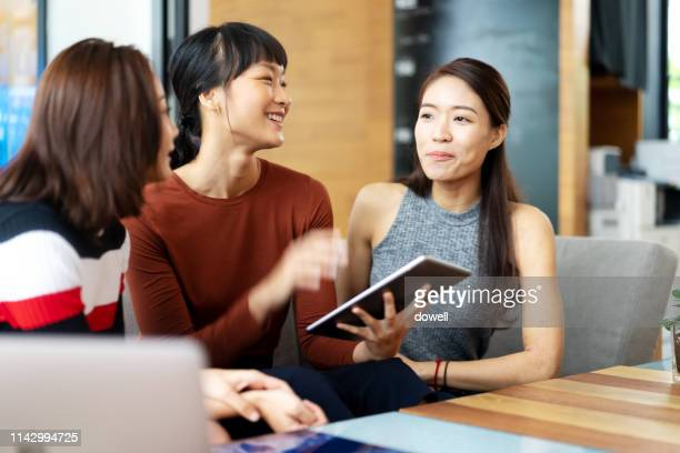 chinese girls talking with digital tablet - chinese ethnicity stock pictures, royalty-free photos & images