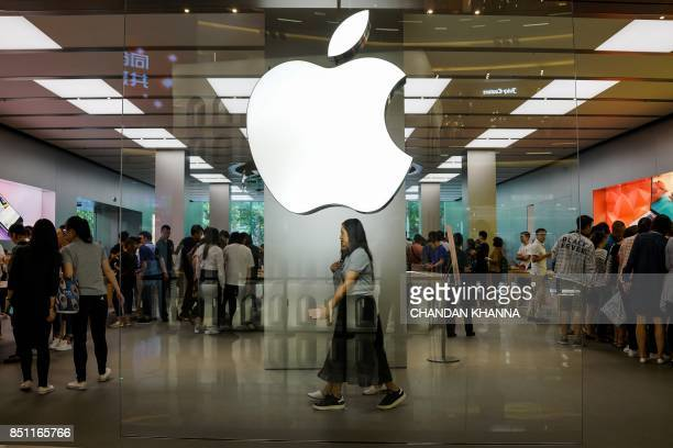 Chinese girls walk inside an Apple showroom in Shanghai on September 22 2017 Apple iPhone 8 and 8 Plus went for sale in China starting September 22...