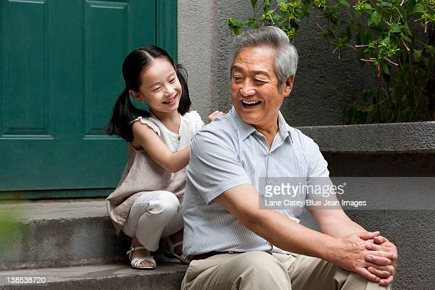 Chinese Grandfather and Grandaughter on front stoop