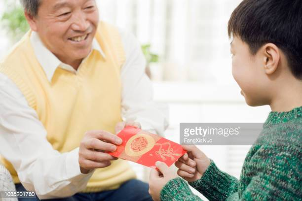 chinese grandfather giving grandson red pocket - chinese new year stock pictures, royalty-free photos & images