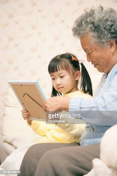 Chinese grandmother with granddaughter looking at framed photo