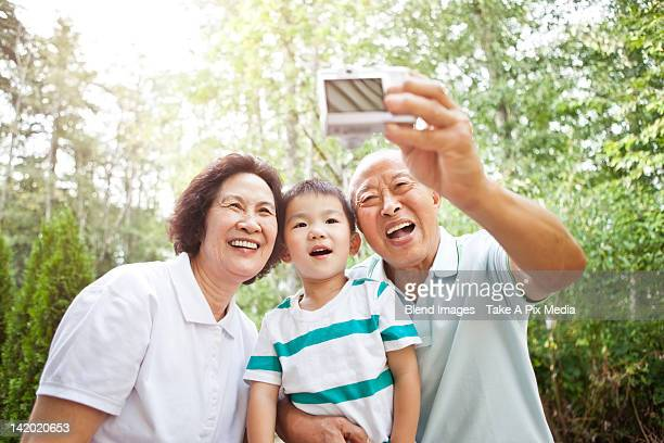 Chinese grandparents taking self-portrait with grandson