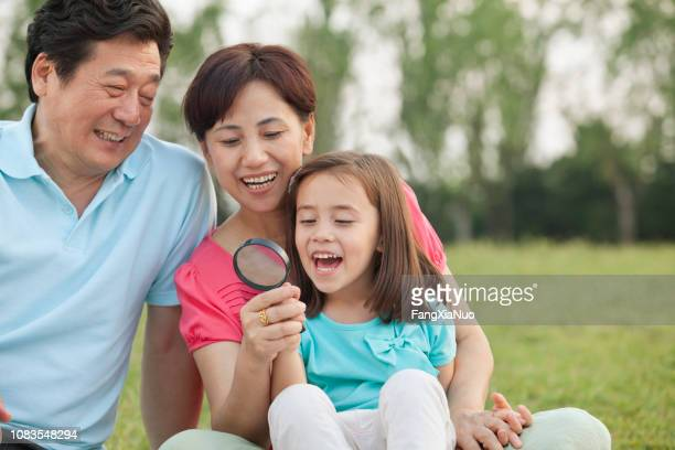 chinese grandparents using magnifying glass with granddaughter - visual china group stock pictures, royalty-free photos & images