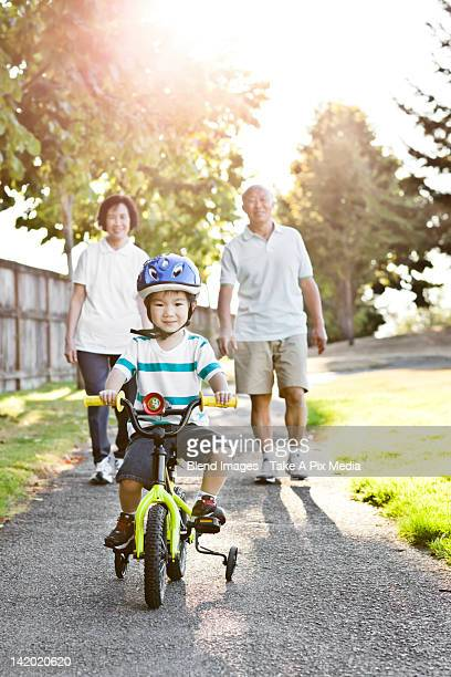 Chinese grandparents watching grandson riding bicycle