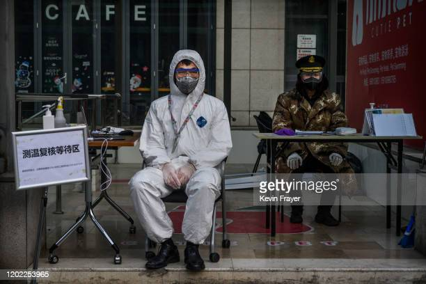 Chinese guard wears a protective mask and suit as he waits to check temperatures and register people entering a building in a commercial area on...