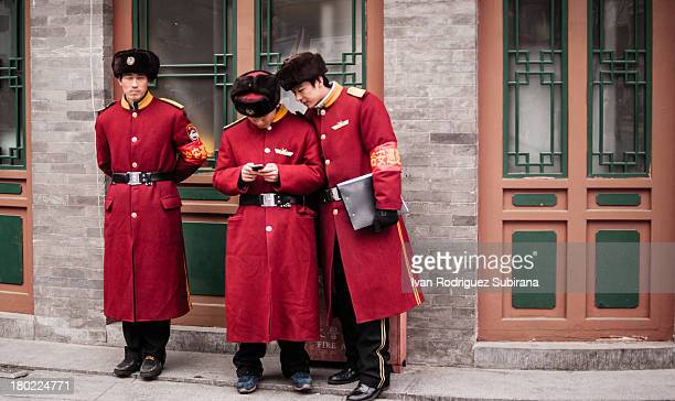 Chinese guards distracted with a cellphone in Qianmen, comercial district of Beijing, China