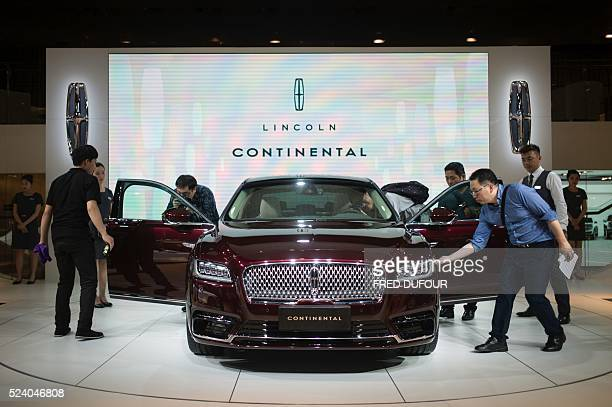 Chinese guests and journalists look at a Lincoln Continental on display at the Beijing Auto Show in Beijing on April 25 2016 Global carmakers...