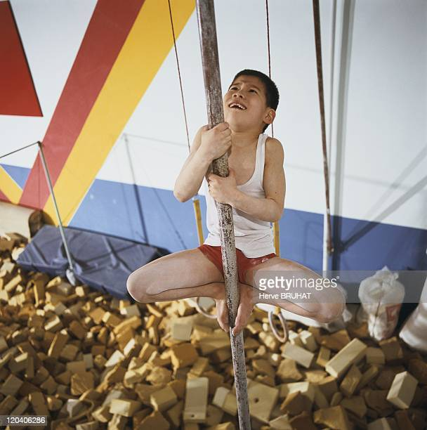 Chinese gymnastics school The professor has the student climb along a bar more than six meters high to fortify his musculature and to help him...